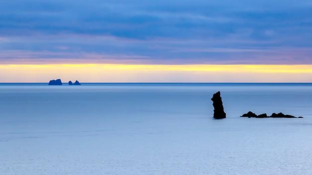저녁 하늘을 배경으로 바다의 바위