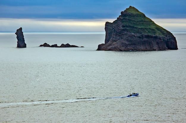 저녁 하늘을 배경으로 바다의 바위 프리미엄 사진