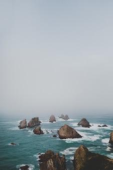 안개 풍경과 바다에있는 바위