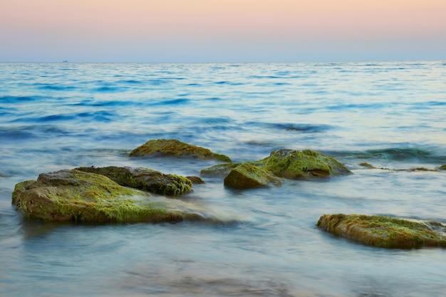 Скалы в море на фоне красивого заката Premium Фотографии