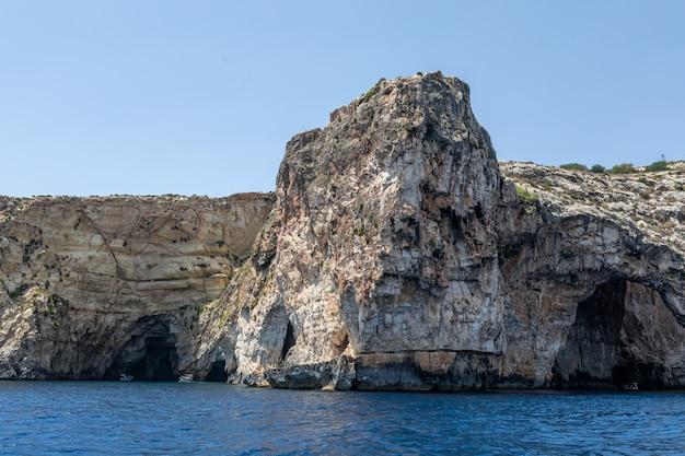 海の岩。海岸の背景の山の斜面。山の風景と海の風景。海の風景の写真。