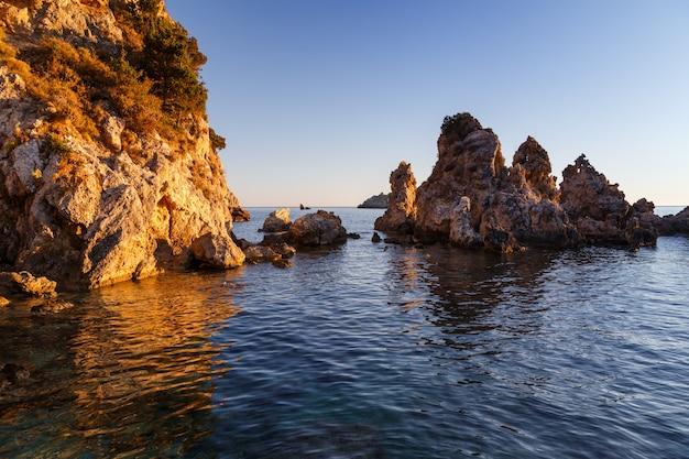Скалы в море отражаются в воде скалистый берег золотой свет греции