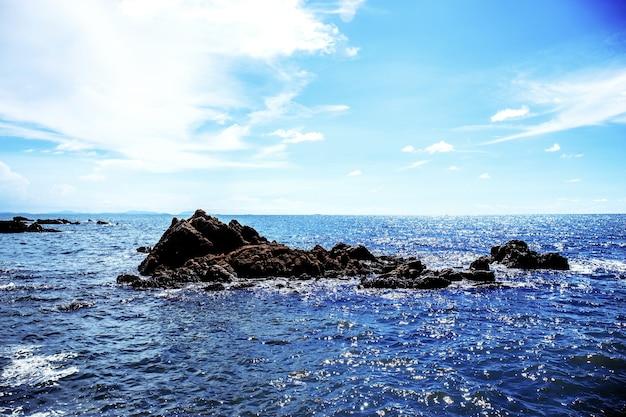 空に日光が差し込む海の岩。