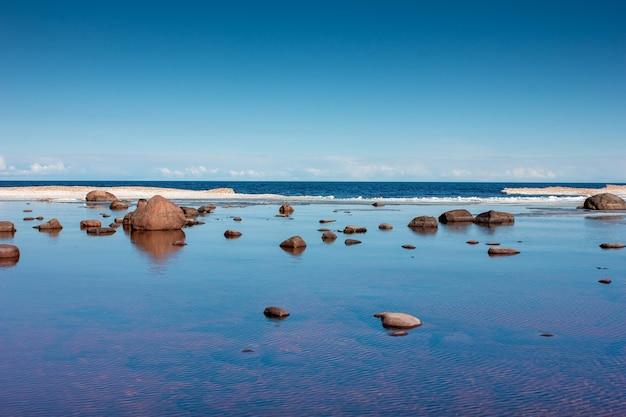 Скалы в воде озера на закате