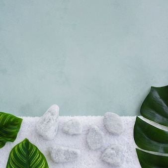 Rocks and leaves on towel with copy space