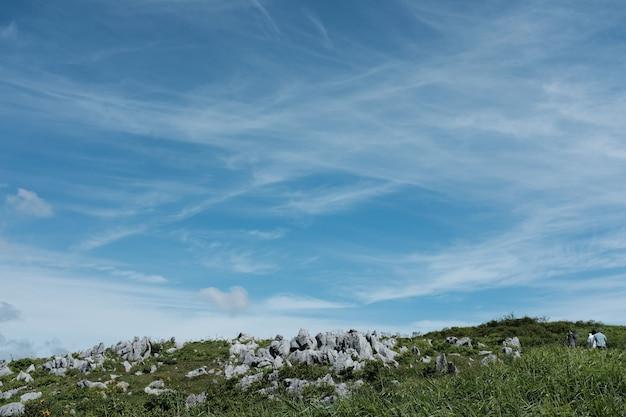 青空の下で草で覆われた丘の上の岩