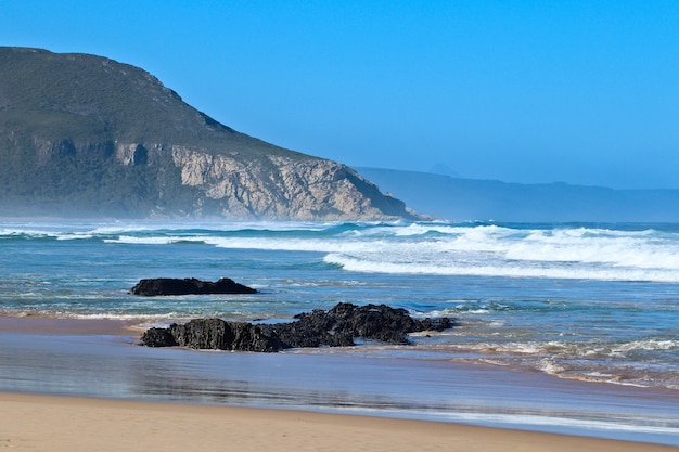 Скалы на пляже у прекрасного океана с горами