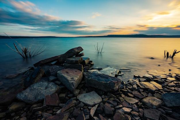 背後に美しい夕日の景色を望む湖の本体の岩