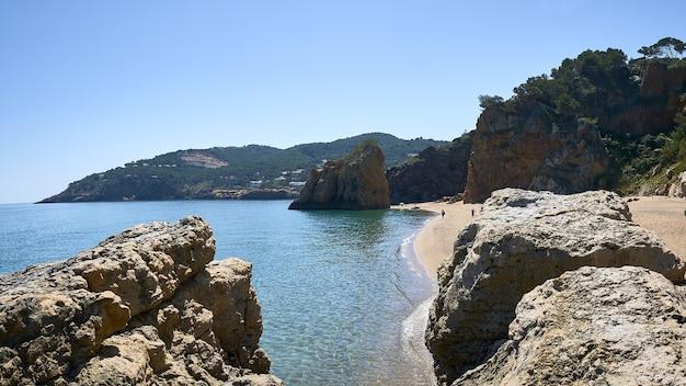 スペインのプラヤイラロハ公共ビーチで海の海岸の岩