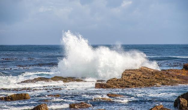 남아프리카 공화국의 낮에는 햇빛 아래 물결 모양의 바다와 흐린 하늘로 둘러싸인 바위