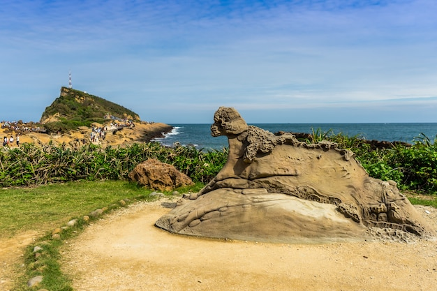 Rocks that are eroded by nature at yehliu geopark and yehliu coast in blur background with blue cloudy sky and sea