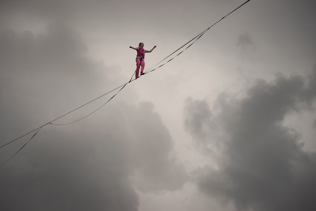 Rocks of a triangular lake, russia - august 2, 2021: a rope-walker girl walks along the highline against the background of a dramatic sky