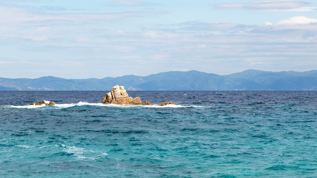 Rocks in the water of the aegean sea with land in the distance in greece