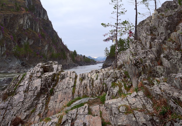 Скалы с вертикальными слоями расходятся веером на берегу горной реки крутая гора