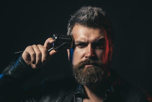 Rocksinger талантливый бородатый певец с микрофоном концепции образа жизни красивый мужчина с бородой и