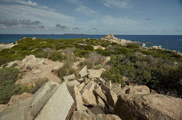 Скалистая и засушливая территория, покрытая средиземноморской растительностью, типичной для южного побережья сардинии, на фоне моря.