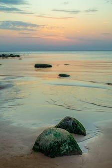 Скалистый пляж рижского залива на закате. каменное побережье видземе в латвии. красивое небо и живописный вид.