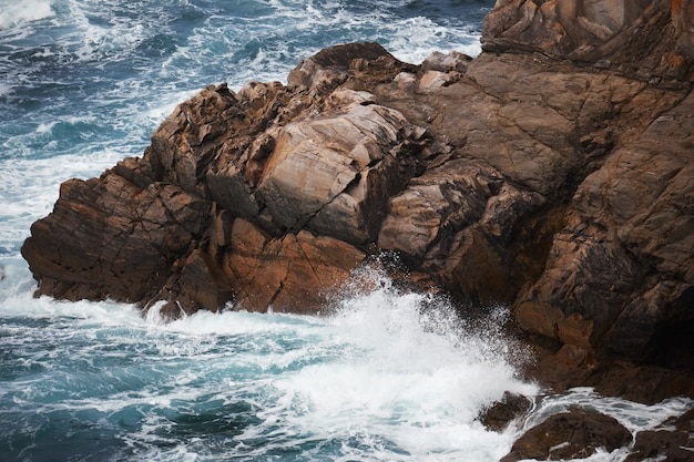 Rocky cliff near a rough body of water with the waves splashing the rocks