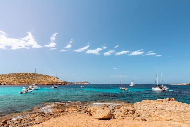 Скалистый берег и чистейшая морская вода острова ибица, испания