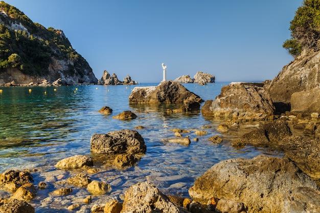 Скалистый берег в палеокастрице корфу греция чистая лазурная вода памятник на одной из скал