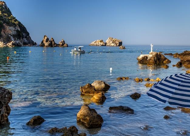 Скалистый берег в палеокастрице, остров корфу, греция, чистая лазурная вода, лодка в море, летние каникулы