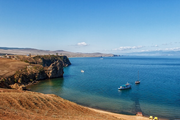 Rocky coast of lake baikal and boats