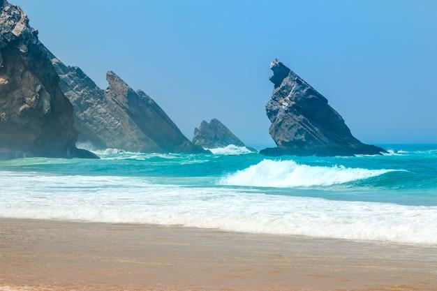 Скалистый берег атлантического океана. солнечная погода и голубое небо. серфинг