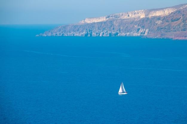 晴れた日のギリシャの島の岩の多い海岸。白いセーリングヨット。航空写真
