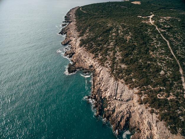 モンテネグロの空中ドローンビューのルスティカ半島の岩の多い海岸泡状の波が海岸に当たる