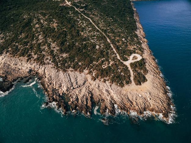 モンテネグロの空中ドローンビューのルスティカ半島の岩の多い海岸泡状の波が海岸にぶつかる