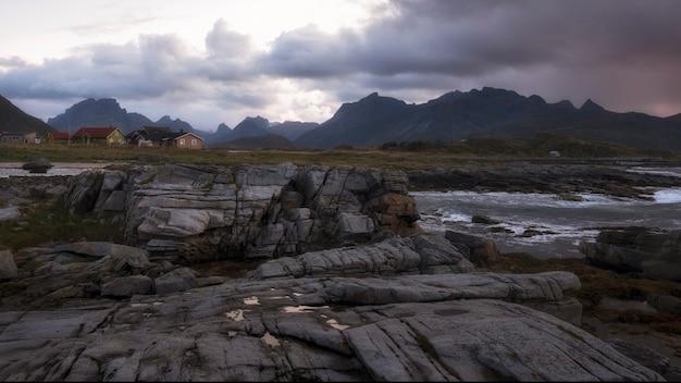 Скалистый берег северного моря в норвегии на лофотенских островах на фоне гор и рыбацкой деревни