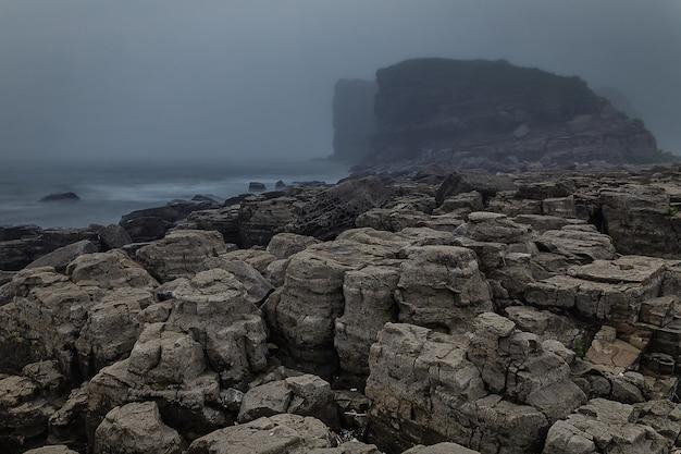 Rocky coastline and high cliffs hidden in mis