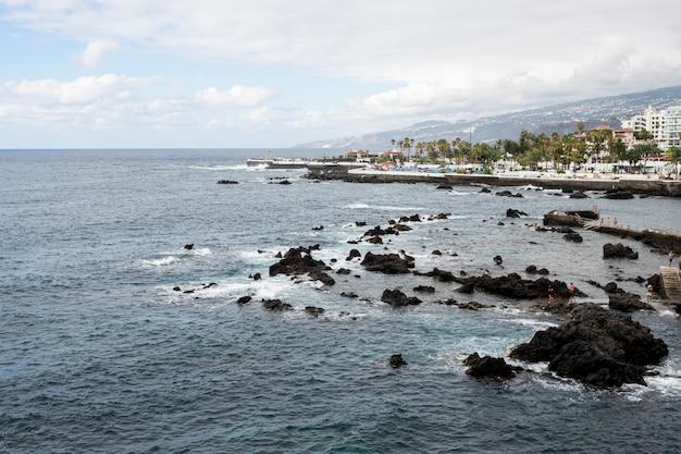 背景に都市と岩の多い海岸線