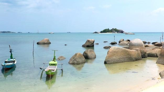 정박된 어선과 잔잔한 바다 전망이 있는 바위 해안선