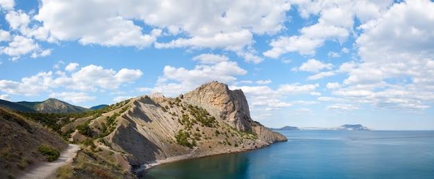 Скалистая береговая линия с соснами, тропой и людьми на пляже