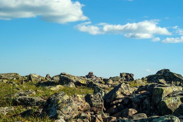 Каменистая травянистая местность на горном перевале и голубое небо с облаками над ним