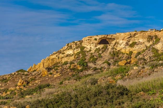 美しい澄んだ青い空の下で緑の植物がたくさんある岩が多い丘