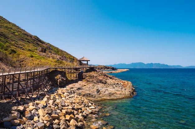 海の近くの木製の橋と岩だらけの島