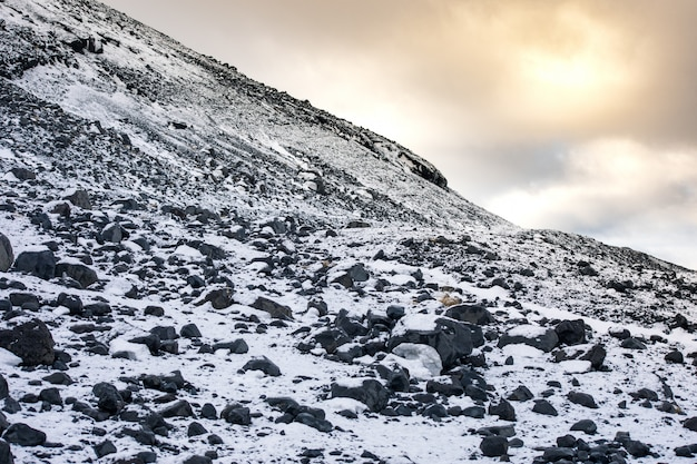 낮 동안 흐린 하늘 아래 눈 덮인 산의 바위 풍경