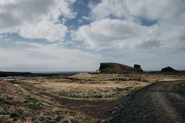 曇り空の下で茂みの多い岩の多い風景