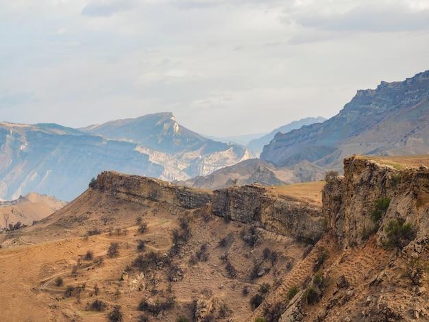 岩だらけの棚、赤い織り目加工の山々を背景に遠くまで伸びる崖。ダゲスタン。 Premium写真