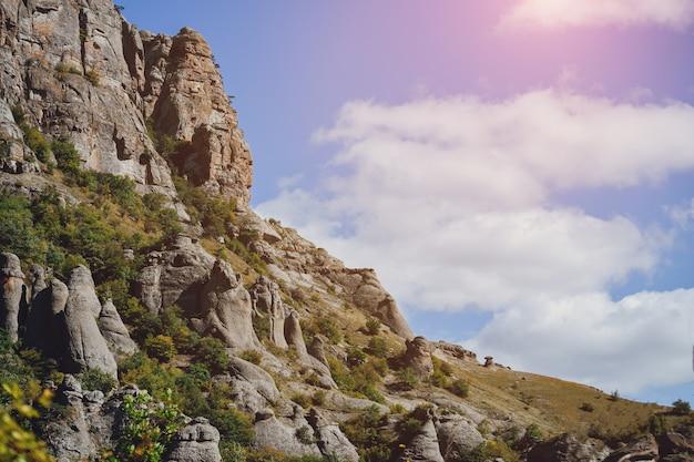 カラフルな雲と空を背景に木々と岩山