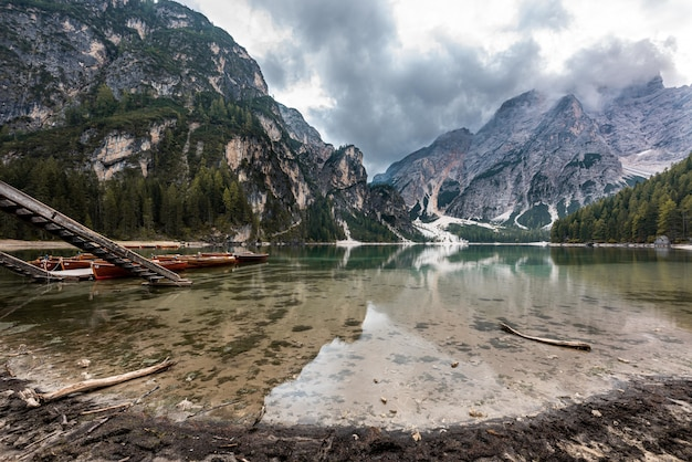 Rocky mountains covered with snow reflected in braies lake in italy under the storm clouds