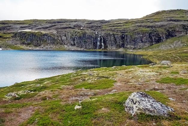 Скалистый норвежский пейзаж с озером и водопадом