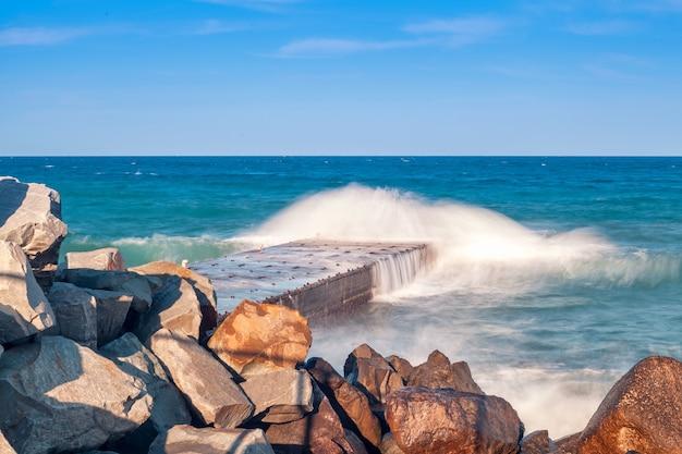 Скалистый берег моря в солнечный день. волны разбиваются о волнорезы и пирс. красивый пейзаж природы летом.