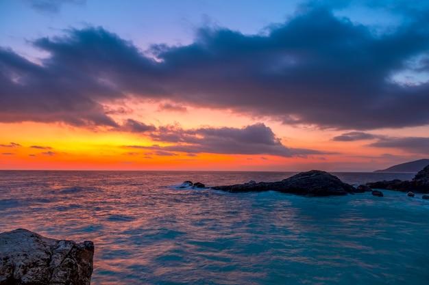 岩の多い海岸。空にはたくさんの雲があり、夜明けまで素晴らしい色があります
