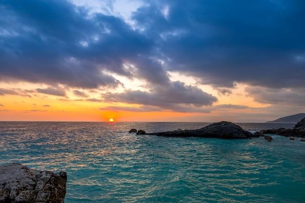 岩の多い海岸。空と太陽の夜明けにたくさんの雲