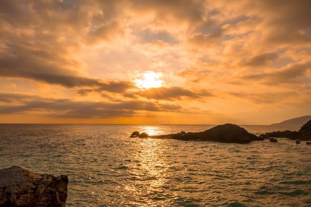 岩の多い海岸。空と太陽光線にたくさんの金色の雲