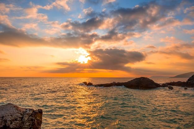岩の多い海岸。空と太陽光線のピンクの雲がたくさん