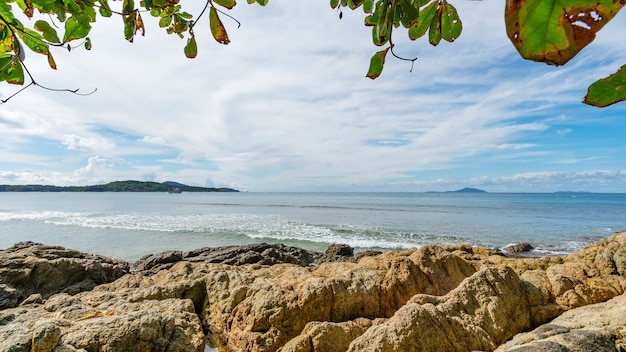 Rocky seashore under clear blue sky with clouds in the morning and leaves trees frame background beautiful sea and small island in phuket thailand.